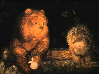 ...Ежик сказал Медвежонку: - Как все-таки хорошо, что мы друг у друга есть! Медвежонок кивнул. - Ты только представь себе: меня нет, ты сидишь один и поговорить не с кем. - А ты где? - А меня нет. - Так не бывает, — сказал Медвежонок. - Я тоже так думаю, — сказал Ежик. — Но вдруг вот — меня совсем нет. Ты один. Ну, что ты будешь делать? - Пойду к тебе. - Куда? - Как — куда? Домой. Приду и скажу: «Ну что ж ты не пришел, Ежик?» А ты скажешь… - Вот глупый! Что же я скажу, если меня нет? - Если нет дома, значит, ты пошел ко мне. Прибегу домой. А-а, ты здесь! И начну… - Что? - Ругать! - За что? - Как за что? За то, что не сделал, как договорились. - А как договорились? - Откуда я знаю? Но ты должен быть или у меня, или у себя дома. - Но меня же совсем нет. Понимаешь? - Так вот же ты сидишь! - Это я сейчас сижу, а если меня не будет совсем, где я буду? - Или у меня, или у себя. - Это, если я есть. - Ну, да, — сказал Медвежонок. - А если меня совсем нет? - Тогда ты сидишь на реке и смотришь на месяц. - И на реке нет. - Тогда ты пошел куда-нибудь и еще не вернулся. Я побегу, обшарю весь лес и тебя найду! - Ты все уже обшарил, — сказал Ежик. — И не нашел. - Побегу в соседний лес! - И там нет. - Переверну все вверх дном, и ты отыщешься! - Нет меня. Нигде нет. - Тогда, тогда… Тогда я выбегу в поле, — сказал Медвежонок. — И закричу: «Е-е-е-жи-и-и-к!», и ты услышишь и закричишь: «Медвежоно-о-о-к!..» Вот. - Нет, — сказал Ежик. — Меня ни капельки нет. Понимаешь? - Что ты ко мне пристал? — рассердился Медвежонок. — Если тебя нет, то и меня нет. Понял? ()